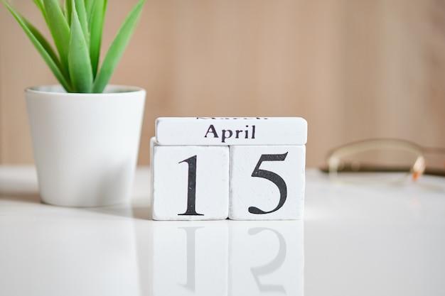 Дата на белых деревянных кубиках - пятнадцатое, 15 апреля на белом столе.