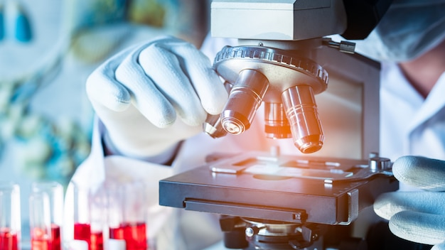 科学者または医師は、顕微鏡下で血液サンプルを見て医療用保護マスクを着用します。16:9スタイル