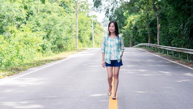 幸せでリラックスした山の道の真ん中を歩いて笑顔のアジア女性16:9スタイル