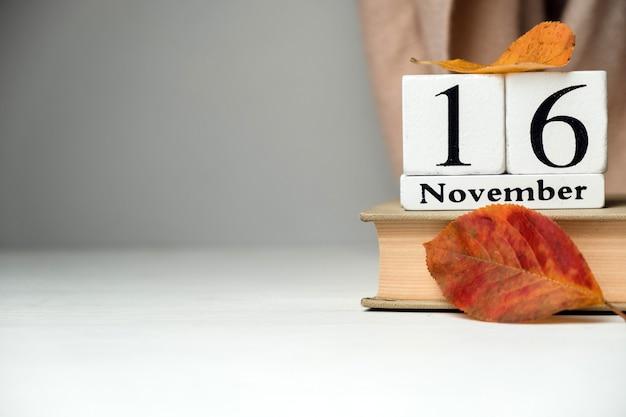 秋の葉の本の白い立方体から作られたカレンダーの11月16日