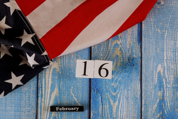 16 февраля календарь красиво размахивая звездой и полосатый американский флаг на старой деревянной доске.