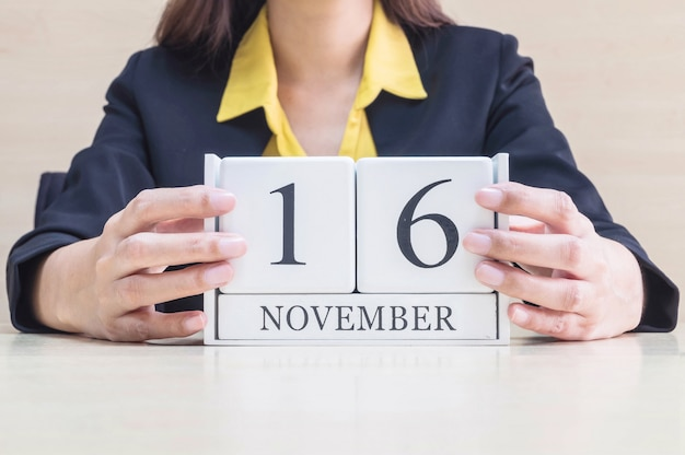Крупным планом деревянный календарь с черным 16 ноября слово на затуманенное работающая рука женщины
