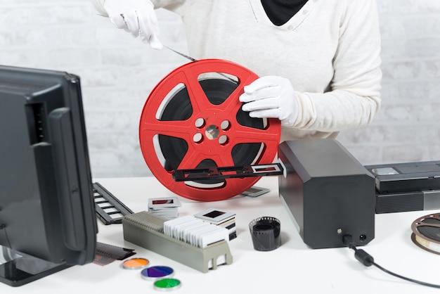16mmフィルムをデジタル化する白い手袋の技術者