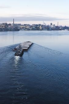 ドニエプル川に浮かぶはしけ。バックグラウンドでキエフ都市景観。 17.11.2018