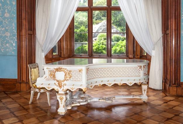 Крым, россия - 17 июня 2015: белое винтажное пианино в стиле ренессанс и барокко
