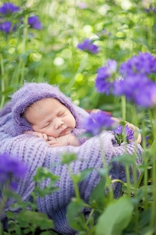 17 day old smiling newborn baby is sleeping on his stomach in the basket on nature in the garden outdoor.