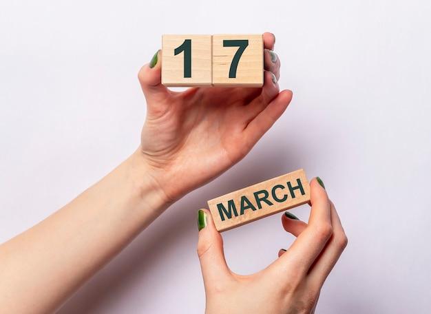 여성의 손에 나무 달력에 3 월 17 일 비문.