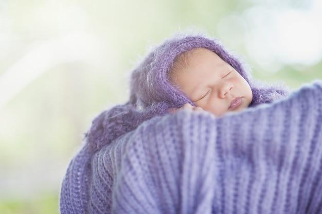 17日の笑みを浮かべて生まれたばかりの赤ちゃんは屋外の庭の自然のバスケットで彼の胃で寝ています。