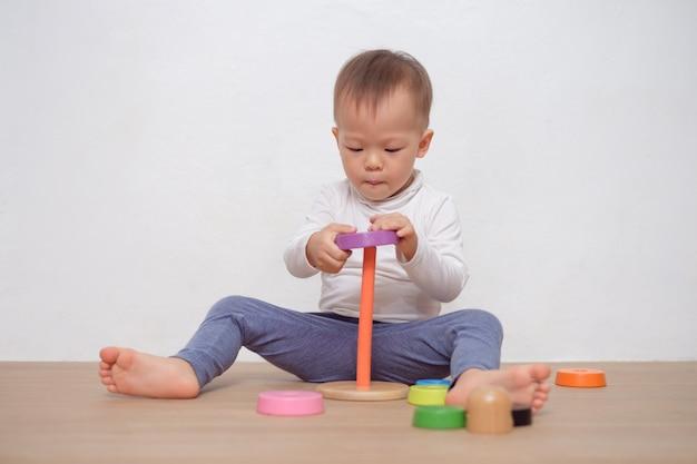 Милая маленькая азиатская детская игра мальчика малыша 18 месяцев / 1 года с красочной деревянной игрушкой пирамиды / игрушкой укладывая кольца. ребенок играет с образовательной игрушкой, изолированной на белой стене, с копией пространства