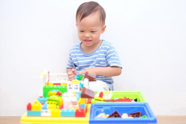 かわいい小さなアジア18ヶ月、1歳の幼児男の子の子供が木の床に座って楽しんでカラフルなビルディングブロックを自宅で屋内で遊んで、幼児の概念のための教育おもちゃ