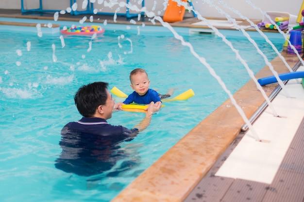 アジアの父はかわいい小さなアジア18ヶ月/ 1歳の幼児の赤ちゃん子供を水泳のクラスに連れて行く
