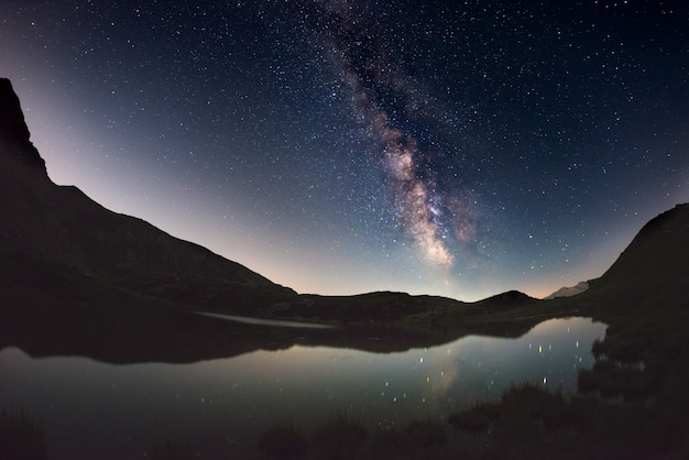 天の川のアーチと星空は、アルプスの標高の高い湖に反映されます。魚眼レンズの景色の歪みと180度のビュー。