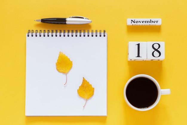 Календарь 18 ноября чашка кофе, блокнот с ручкой и желтый лист на желтом фоне