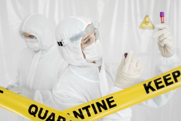 コロナウイルスコビッド19研究所、コロナウイルスコビッド-19ワクチン研究室の科学者医師のバイオハザード防護服を手にしたサンプルチューブ内のコロナウイルスコビッド19感染血液サンプル