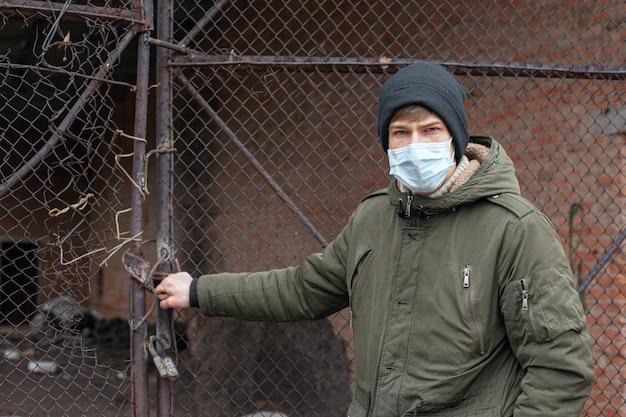 放棄された建物の近くの医療マスクの若い男。呼吸器ウイルス性疾患流行性コビッド19麻疹インフルエンザ水chicken。
