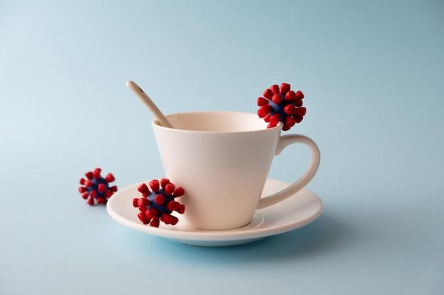 Белая чашка с моделями вируса ковид-19. эпидемический коронавирус. риск заражения концепцией covid-19.
