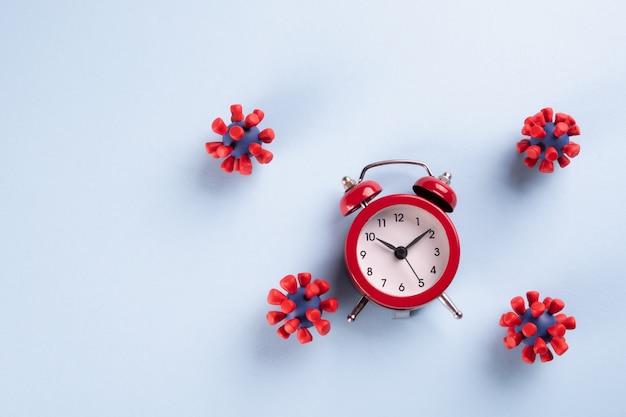 Пандемия коронавируса. время оставаться дома красный будильник и и модели вируса ковид-19. остановить коронавирус. эпидемия, социальная изоляция, коронавирусная концепция covid-19.