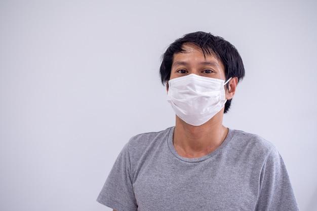 コロナウイルスやコビッド19、有毒な煙や塵から保護するためにマスクを着用しているアジア人男性の顔の画像。 pm 2.5