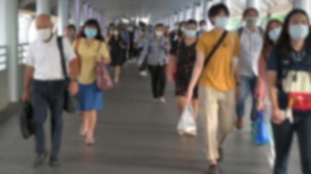 デフォーカスぼかし。群衆は防護マスクを着用して、ウイルスの発生中のコロナウイルス、コビッド19ウイルス、pm2.5大気汚染危機ラッシュアワー、タイのバンコクを防ぎます。