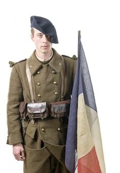 白い背景で隔離の旗を持つ1940年フランスの兵士