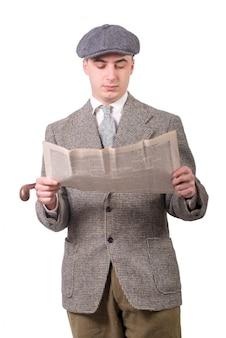 Молодой человек в винтажной одежде с шляпой, читает газету, стиль 1940 года