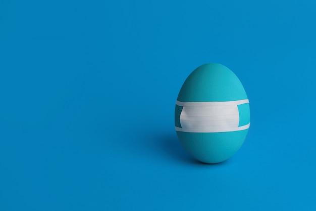 Одно голубое пасхальное яйцо в маске защитной медицины на голубой предпосылке. пасха на карантине концепции с местом для текста. стоп вирус ковид-19. защитная маска ручной работы. копировать пространство