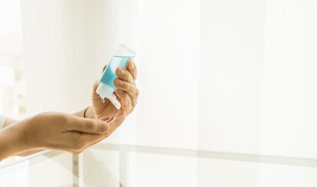 ヘルスケア、ウイルス、コロナウイルス、コビッド19、保護の概念。一方でアルコールゲル消毒剤を使用して人間の手のクローズアップ。