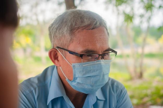 Старик использует маску для защиты от коронирусного вируса 19 при общении с людьми