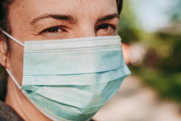 Женщина в защитной хирургической маске от заболевания ковид-19