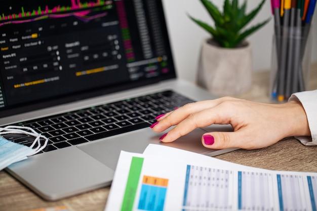Грустная женщина смотрит на падающие графики акций во время эпидемии ковид-19