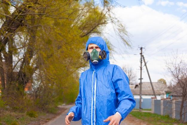 保護用の青いオーバーオールスーツと路上に立っているマスクのマスク、検疫の安全対策、大流行の流行病19の男。