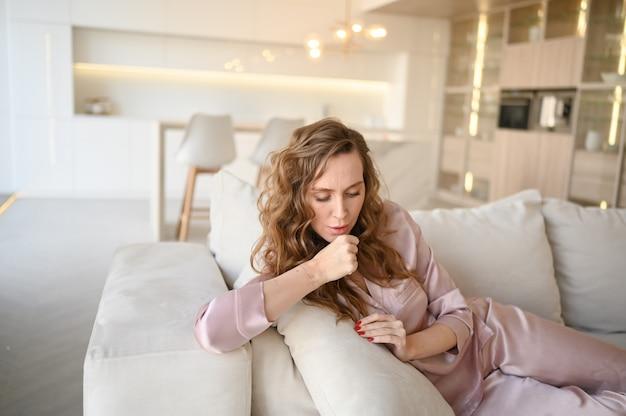 Симптомы ибс (ковид-19) - насморк, боль в горле, кашель, лихорадка. молодая женщина в розовой пижаме, лежа на диване у себя дома на карантине