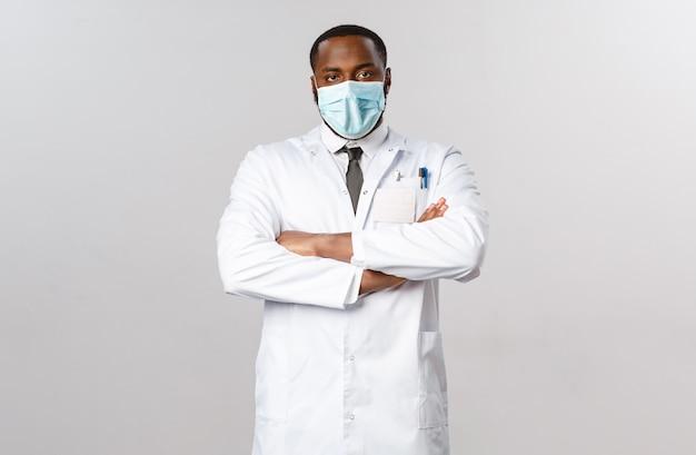 Серьезно выглядящий разочарованный афроамериканский доктор, выглядящий скептически и уставшим от человека, не соблюдающего рекомендации по карантину «ковид-19», грудь со скрещенными руками, пристальный взгляд, надеть белое пальто