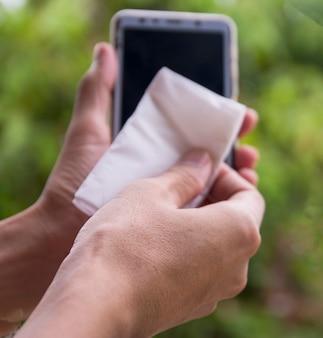 柔らかい紙で携帯電話の画面をクリーニングします。コロナウイルス、コビット-19予防と消毒。