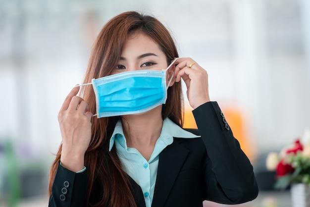 コビッド19ウイルスの拡散後にマスクを着た美しいビジネスウーマンは、細菌や細菌の拡散を防ぎ、冠状動脈性心臓病を回避します。