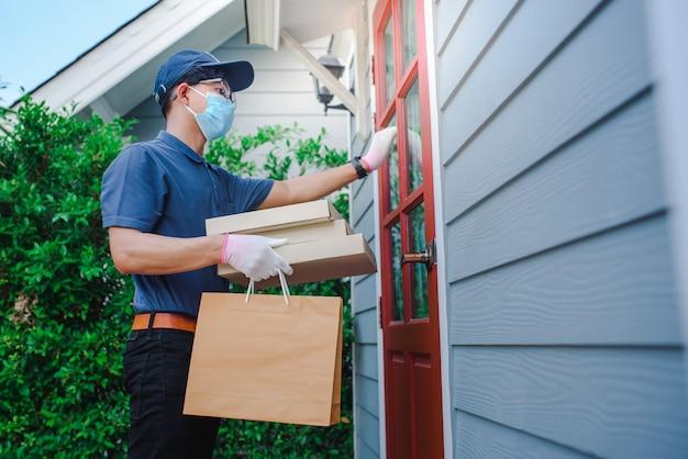 オンラインで注文された商品を配達するアジア人男性。自宅からオンラインで注文するお客様に製品をお届けしますコロナまたはコビッド-19を保護するために医療用マスクを着用してください。