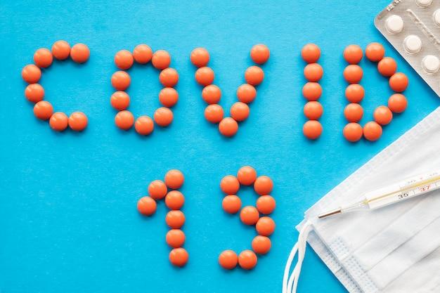青色の背景に薬とスペル単語コビッド19。ウイルスの概念を停止します。