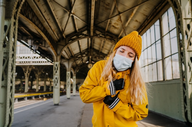 Блондинка в медицинской маске, одетая в желтую куртку, с трудом дышит, прикрывая грудь глазами на фоне пустого железнодорожного вокзала. коронавирусная оболочка-19 концепт