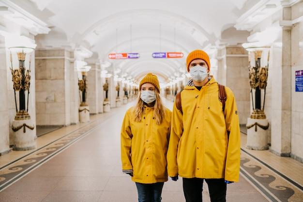 ウイルスカバー19について考える空の地下鉄駅で黄色の防風服を着た防護マスクの若いカップル。コロナウイルスのパンデミックのコンセプト。