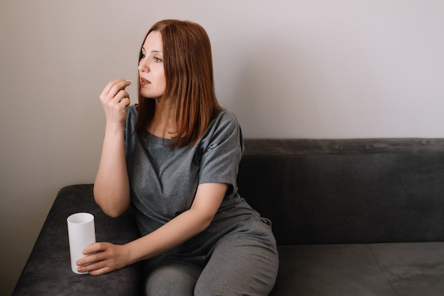 Женщина принимает таблетки витамина, сидя на диване в гостиной дома. проблема коронавируса и концепция защиты ковид-19.