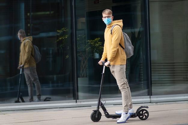 Красивый парень, молодой человек в защитной стерильной медицинской маске и очки на его лице, езда на электрической городской современный скутер с рюкзаком. коронавирус, вирус, эпидемия ковид-19, экологическая транспортная концепция.