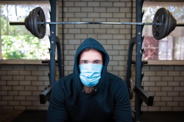 重みと防護マスクと手袋、コロナウイルス、コビッド19、フィットネス、コロナの概念のためのジムで若い男