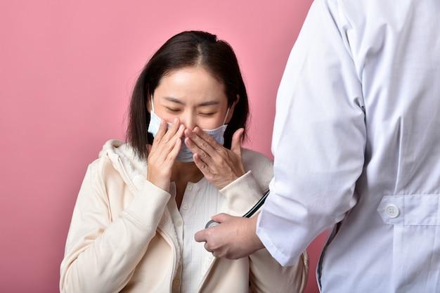 У азиатской женщины есть аллергия на горло и кашель в маске, чихание и кашель, распространяющаяся капелька коронавирусной болезни, доктор осматривает больного, инфицированного ковид-19, в больнице.