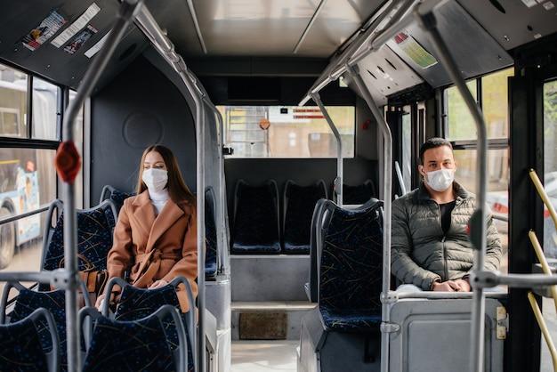 Пассажиры в общественном транспорте во время пандемии коронавируса держатся на расстоянии друг от друга. защита и профилактика ковид 19.