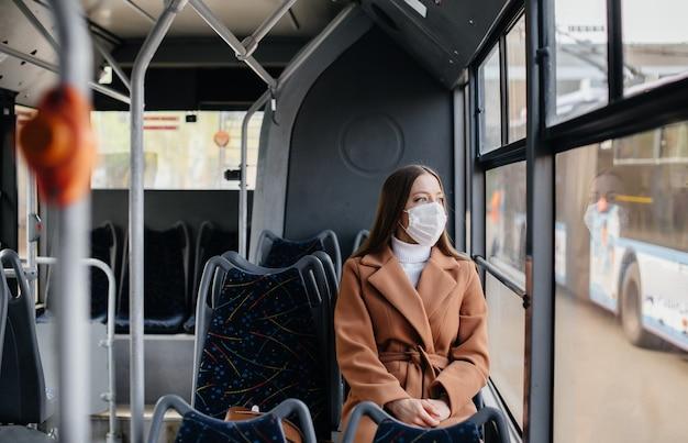 Молодая девушка в маске пользуется общественным транспортом в одиночку, во время пандемии. защита и профилактика ковид 19.