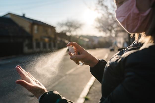 コロナウイルス。市内の消毒スプレーで手を掃除します。路上で医療用防護マスクを着ている女性。コロナウイルス、コビッド-19、インフルエンザを防ぐための消毒剤。スプレー・ボトル。ウイルスと病気の保護。