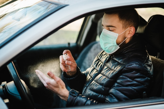 抗菌消毒スプレーを手に車にスプレー、感染管理のコンセプト。コロナウイルス、コビッド-19、インフルエンザを防ぐための消毒剤。スプレー・ボトル。車を運転して医療用防護マスクを着た男。