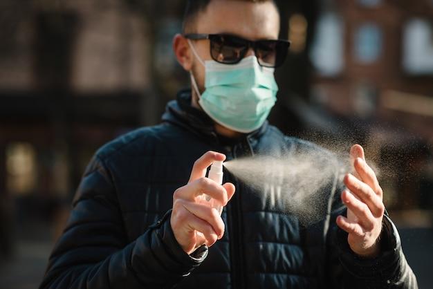 コロナウイルス。市内の消毒スプレーで手を掃除します。通りの医療防護マスクを着た男。コロナウイルス、コビッド-19、インフルエンザを防ぐための消毒剤。スプレー・ボトル。ウイルスと病気の保護。