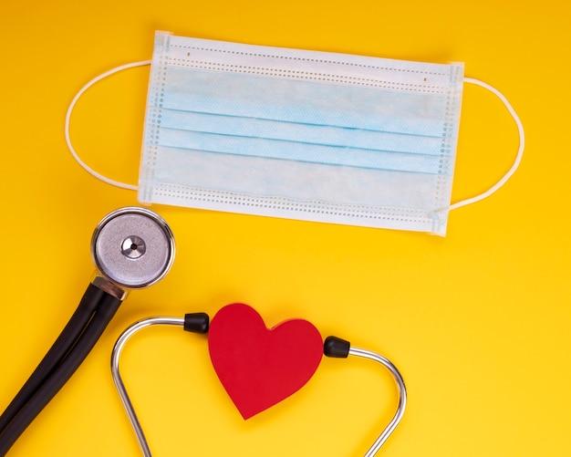 Стетоскоп, медицинская маска для рта, защита красного сердца от ковид-19, вирус, коронавирус. здравоохранение и медицинская концепция, желтая предпосылка.