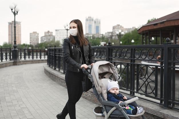 Женщина с маской для защиты от коронавируса, ковид-19 толкает коляску на улице